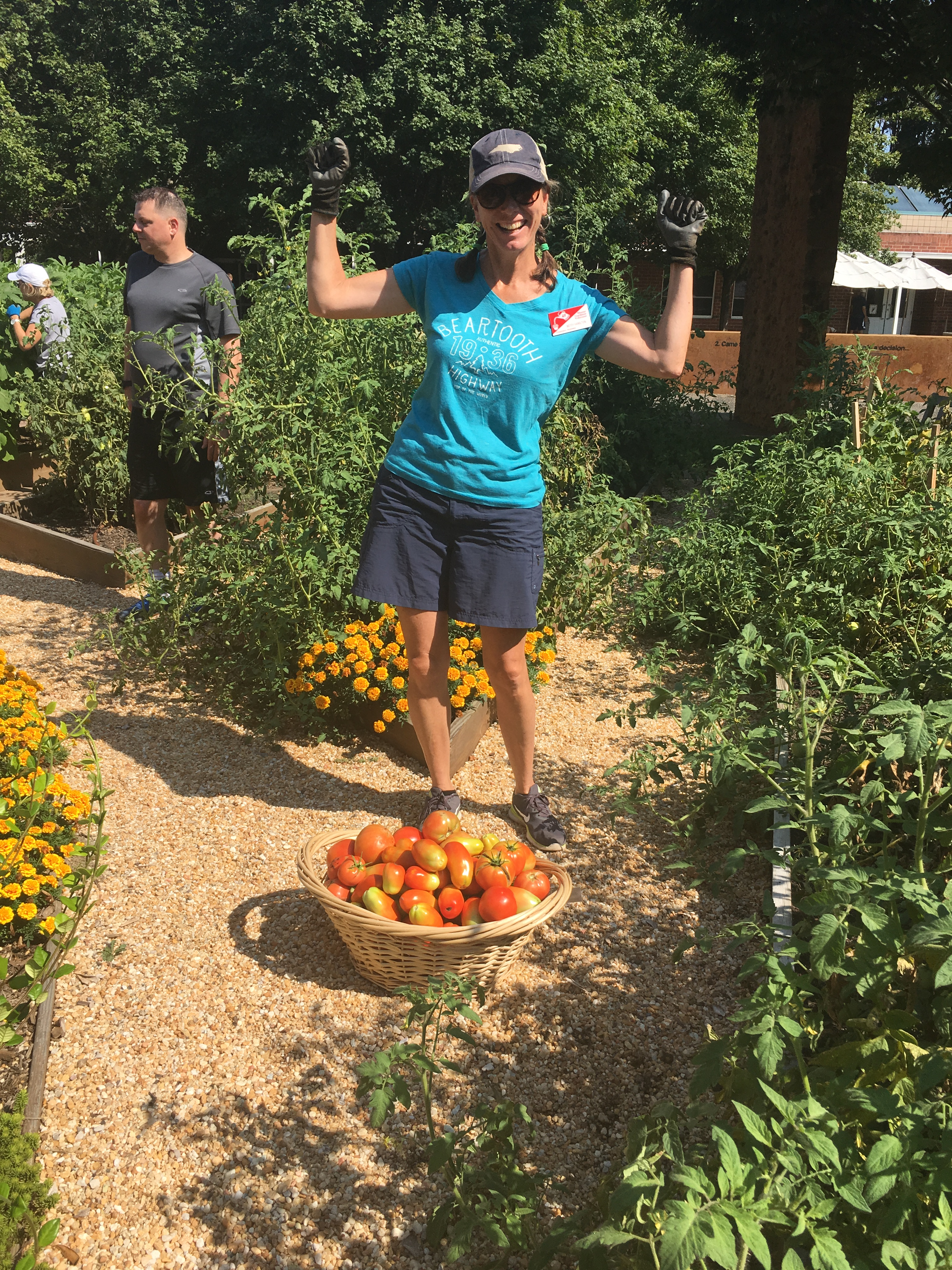 An Extension Master Gardener Volunteer poses excitedly in front of a basket of tomatoes.