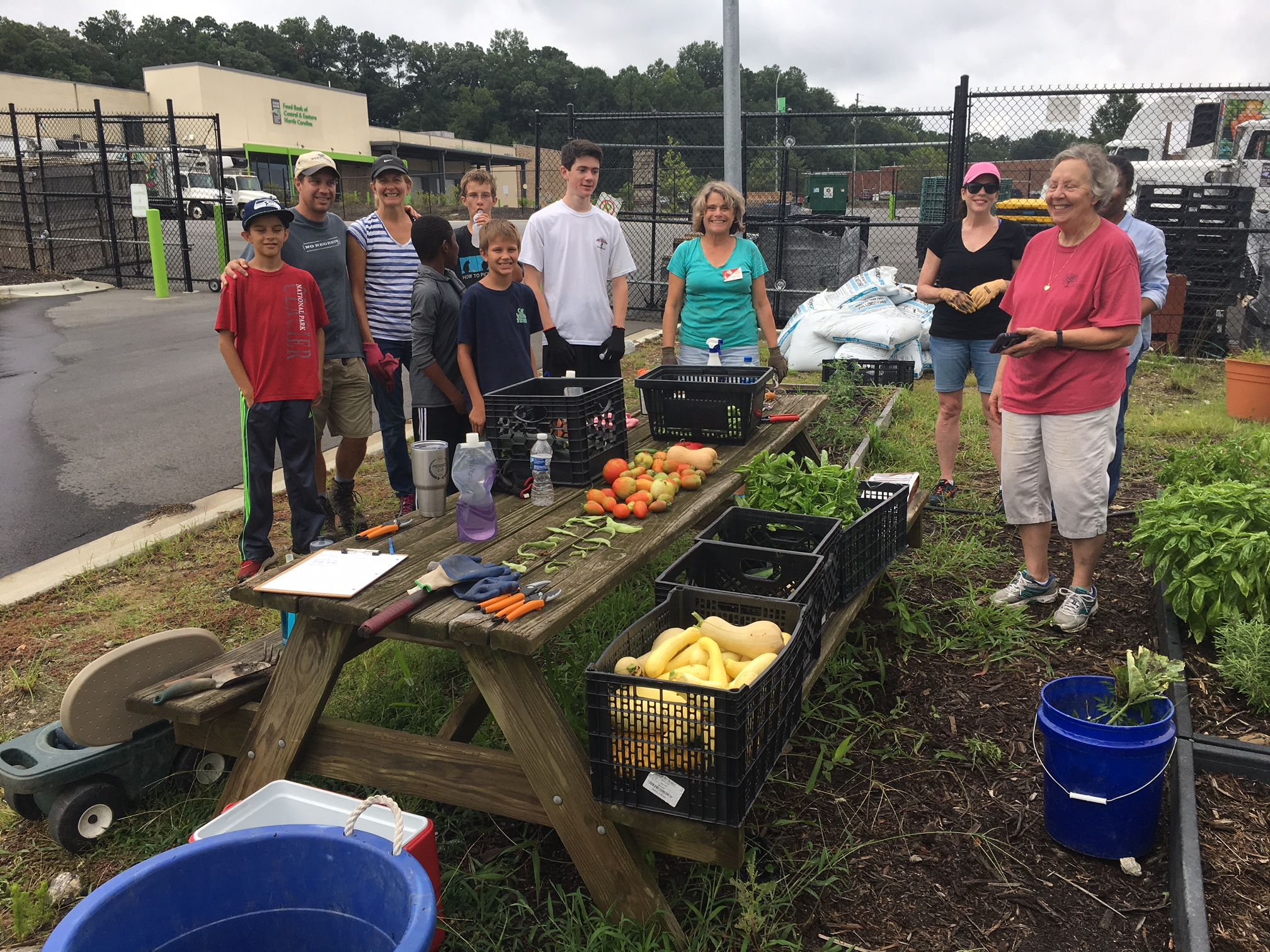 A group of volunteers stand with Extension Master Gardener Volunteers at the food bank of central and eastern north carolina's community and demonstration garden